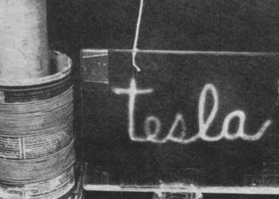 The word TESLA illuminated by high-frequency alternating current.