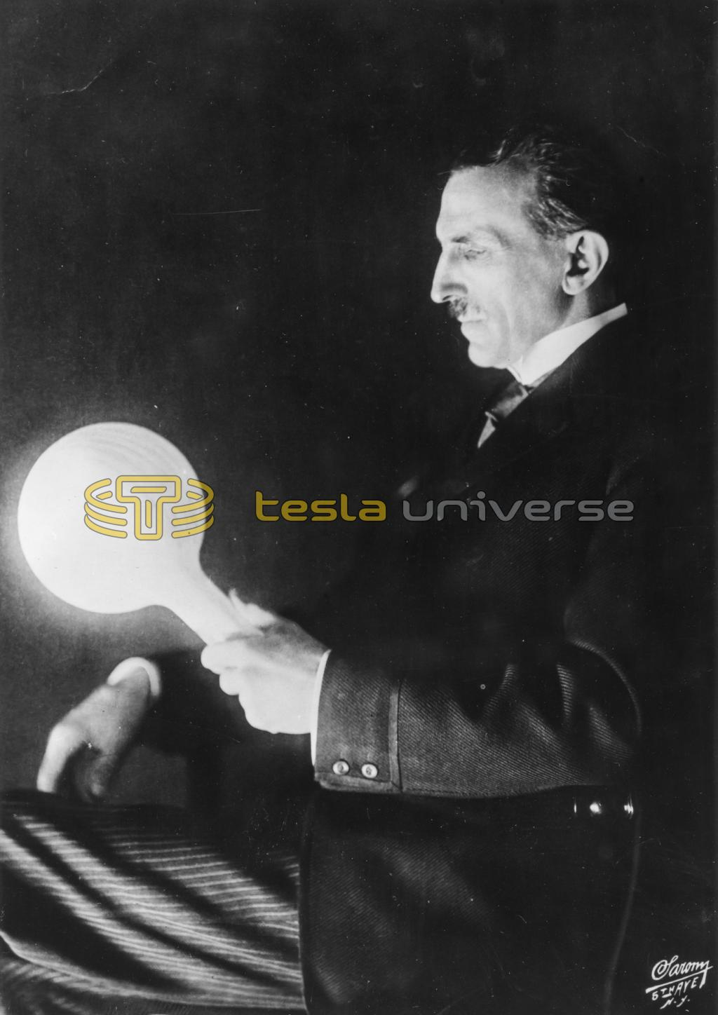 Nikola Tesla holding filamentless bulb lit by wireless power