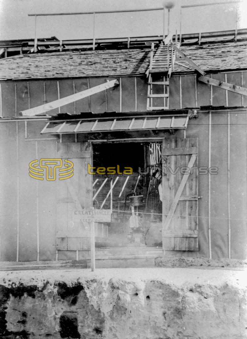Tesla peeks out the door of the Colorado Springs laboratory, early summer 1899