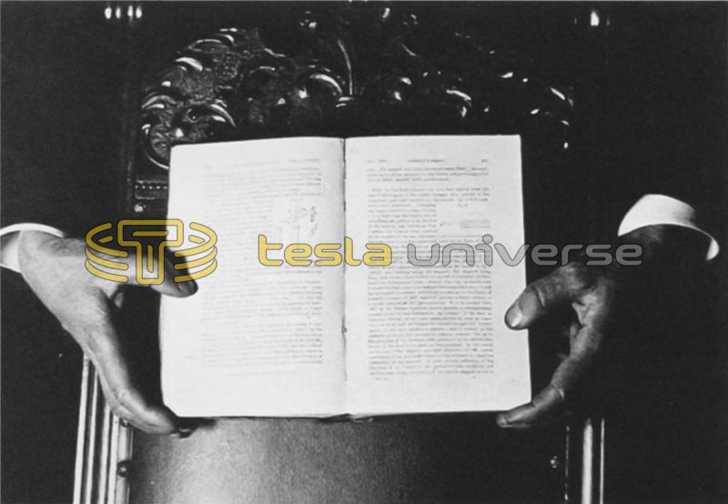 The hands of Tesla holding a book for a photo using fluorescent light